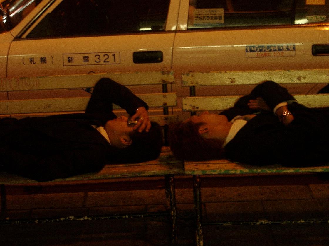 Insolite : Businessmen allongés sur un banc après le travail se protégeant les yeux de la lumière environnante avec leur téléphone portable (Sapporo)