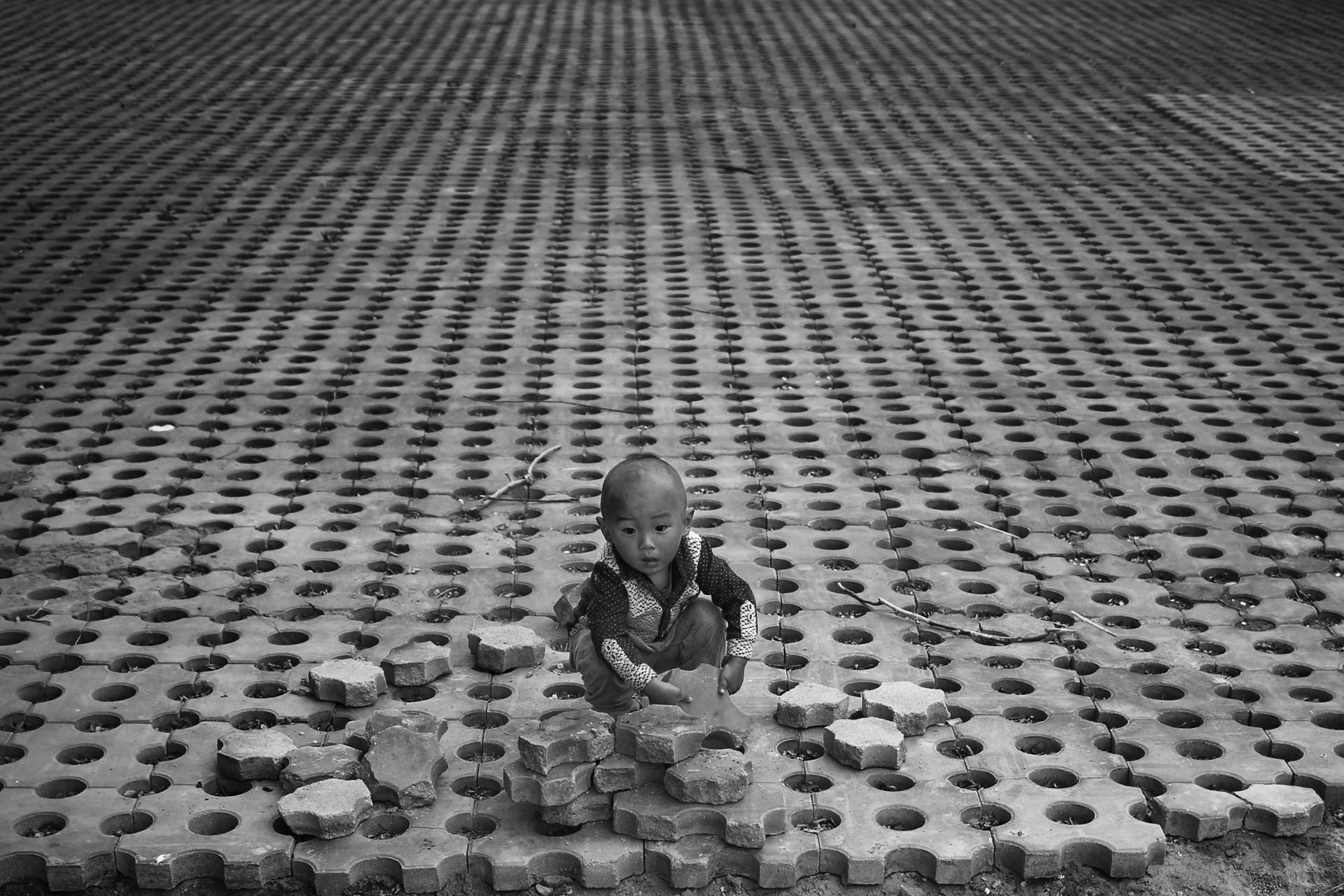 Portrait de rue - Enfant jouant avec des pavées a Pekin