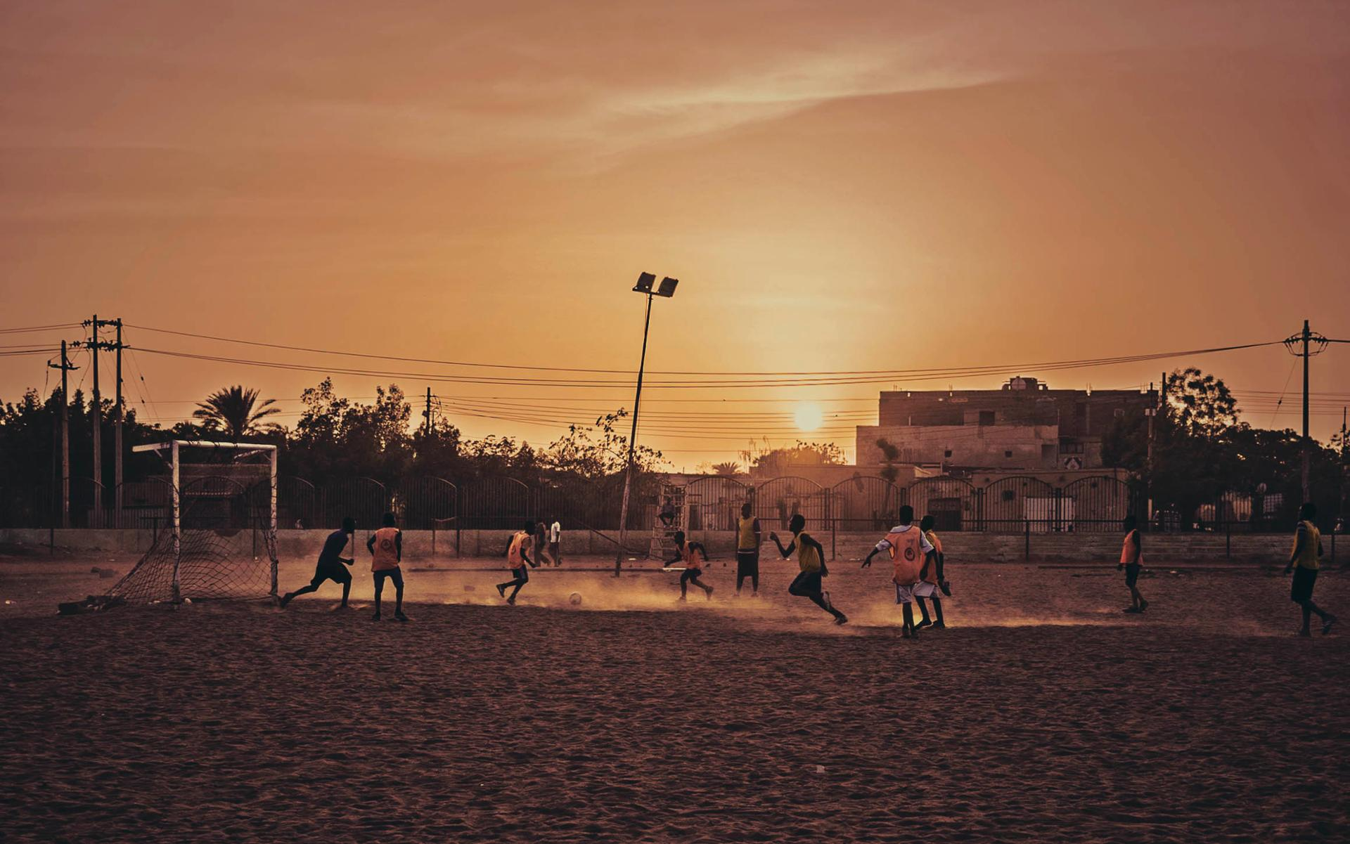 Sudan kids playing football at sunset