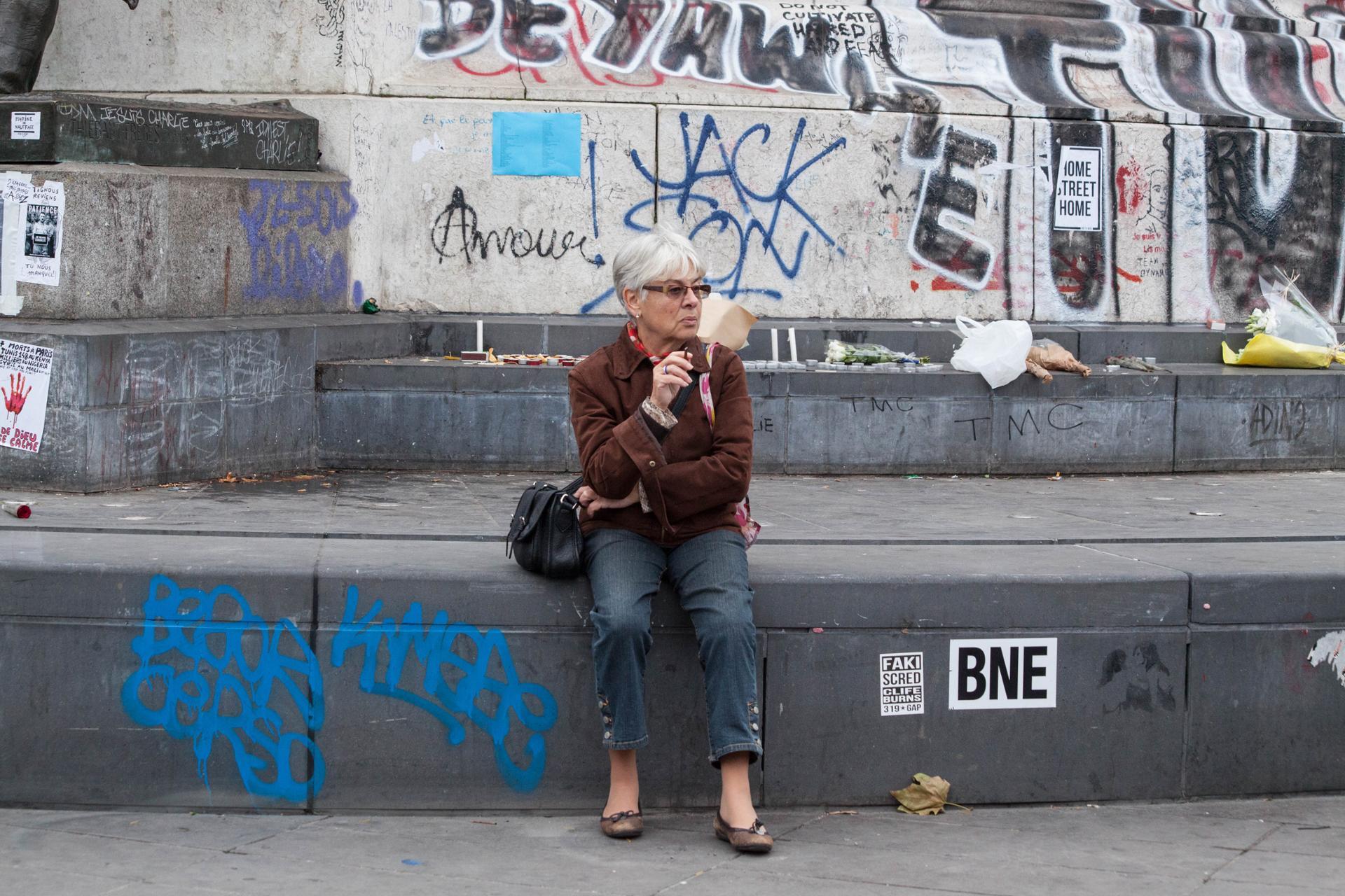 Une dame fumant au pied du monument de la Place de la République le lendemain des attentats de Paris.