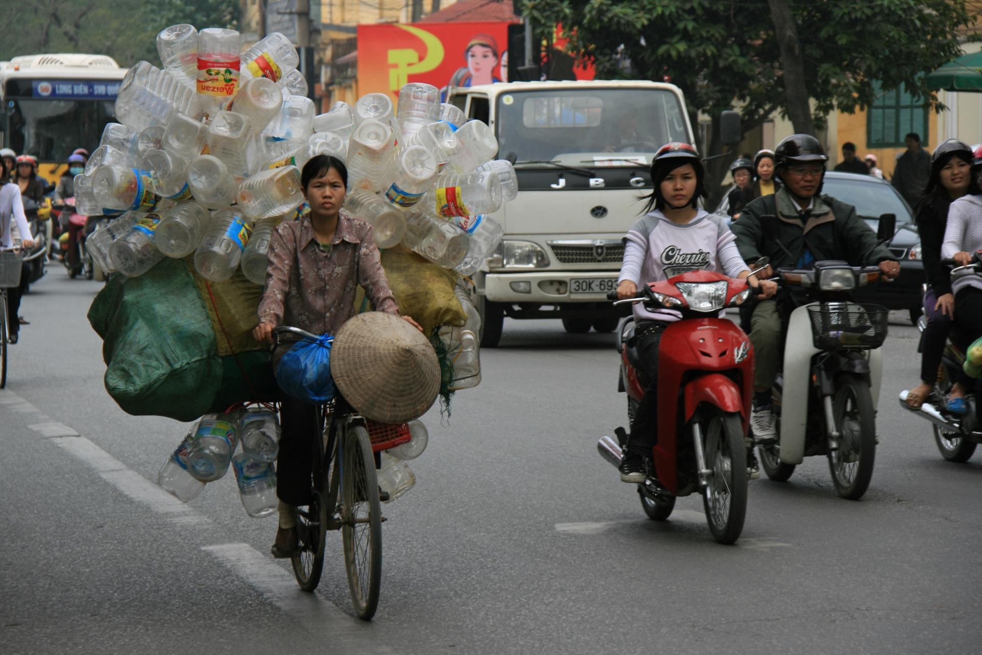 A woman is transporting plastic bottles on her bike in a street of Hanoi (Vietnam).